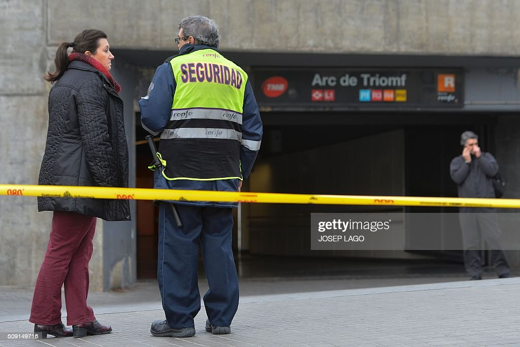 A woman talks to a security guard in front of a temporarily closed subway station following a fire at an abandoned underground station in Barcelona on February 9, 2016. Barcelona's railway network was brought to a standstill for several hours today affecting some 72,000 passengers during rush hour after a fire brokeout in an unused subway station. / AFP / JOSEP LAGO