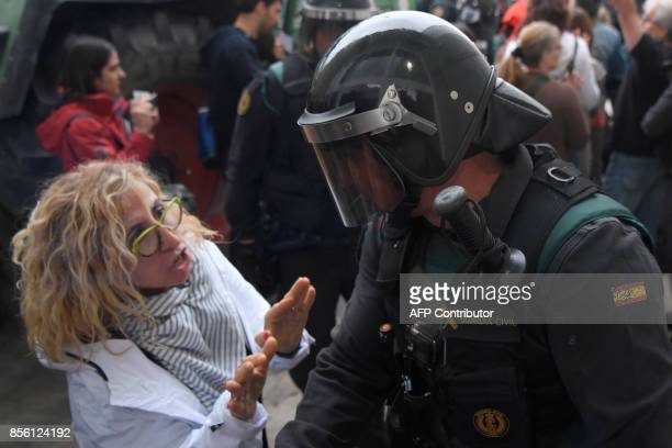 A woman talks to a Spanish Guardia Civil guard outside a polling station in Sant Julia de Ramis where Catalan president is supposed to vote on...