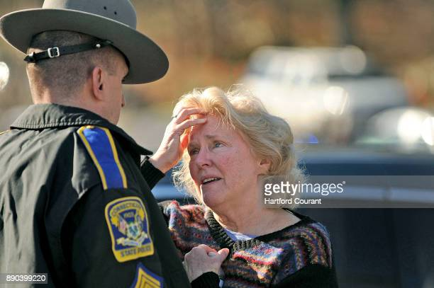 A woman talks to a state police officer at the scene of a shooting at Sandy Hook Elementary School in Newtown Connecticut Friday December 14 2012...