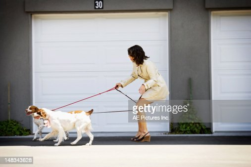 Woman tangled up in her dog's leashes