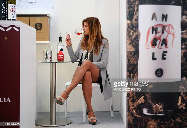 A woman tastes a wine from the 'Le Moire' wine maker of the Italian Calabria region on March 25 2012 at the Vinitaly exposition in Verona The 46th...