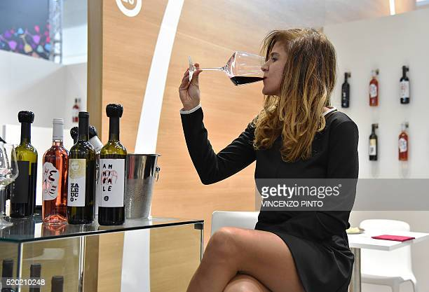 A woman tastes a wine from the 'Le Moire' wine maker of the Italian Calabria region on April 10 2016 during the 50th edition of the Vinitaly wine...