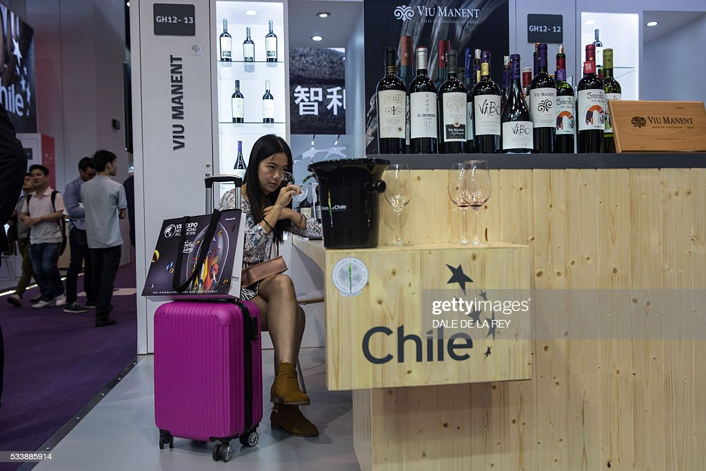 A woman (C) tastes wine during Vinexpo in Hong Kong on May 24, 2016. The international wine and spirits exhibition runs from May 24 to 26. / AFP / DALE