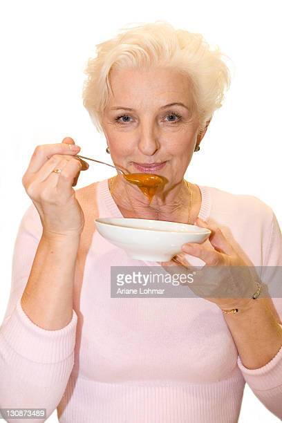 A woman tasting curry sauce off a spoon
