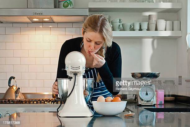Woman tasting dough mix