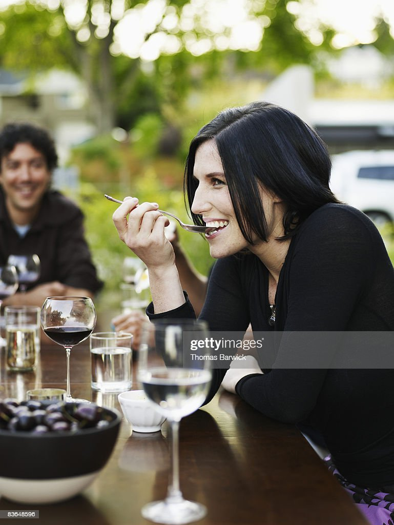 Woman tasting gelato at outdoor dining table : Stock Photo