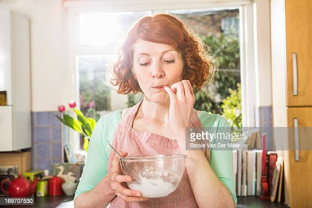 Woman tasting icing for cakemaking.