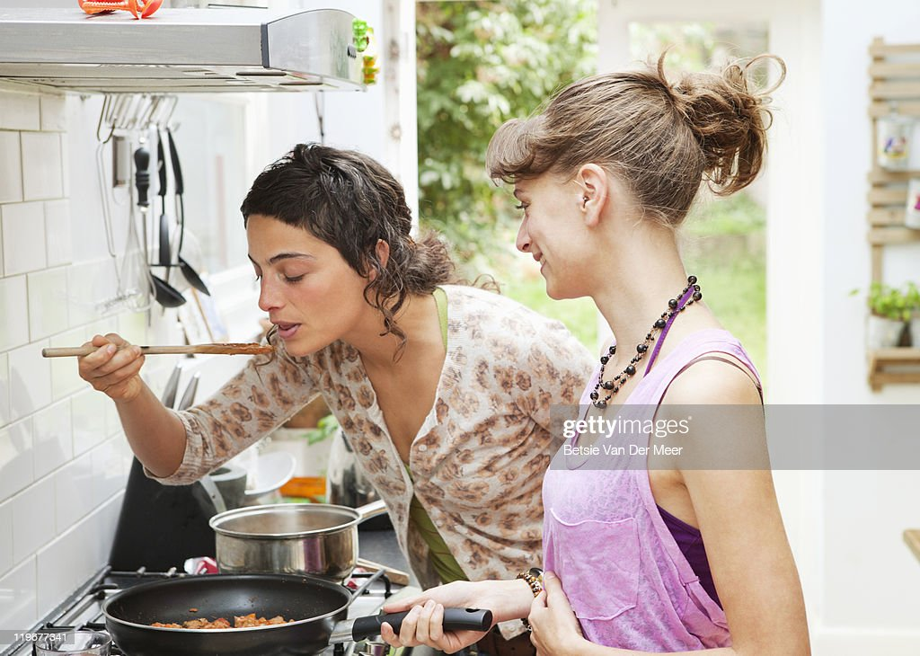 Woman tasting pasta sauce while friend looks on. : Stock Photo