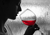 Woman tasting glass of red wine.