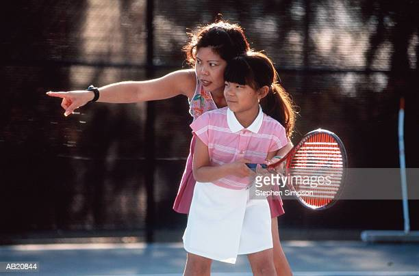 Woman teaching girl (11-13) to play tennis