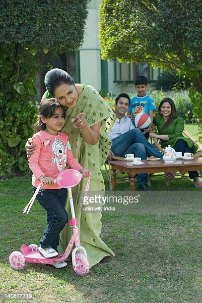 Woman teaching her granddaughter how to ride a push scooter with family in the background