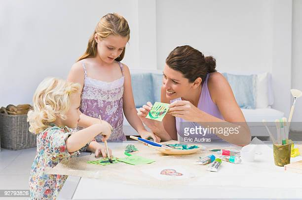 Woman teaching her two daughters
