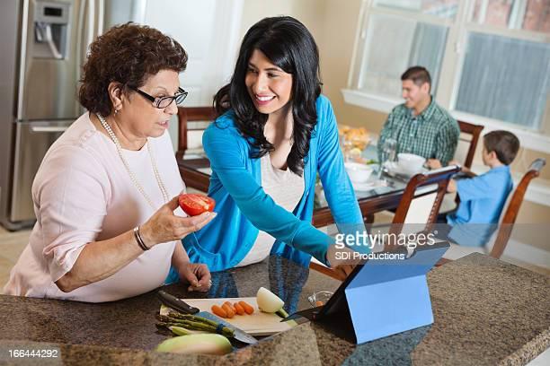Femme senior mère enseignement à utiliser pour tablette en cuisine