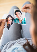 Woman tearing picture of herself with ex-boyfriend