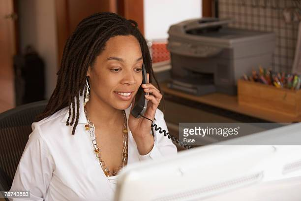 Woman Telephoning and Working on Her Computer