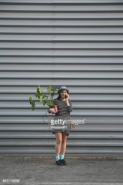 Woman telephoning with smartphone carrying a Monstera deliciosa