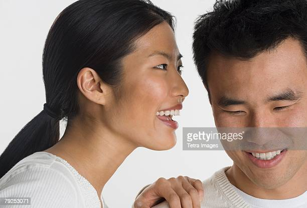 Woman telling man a secret