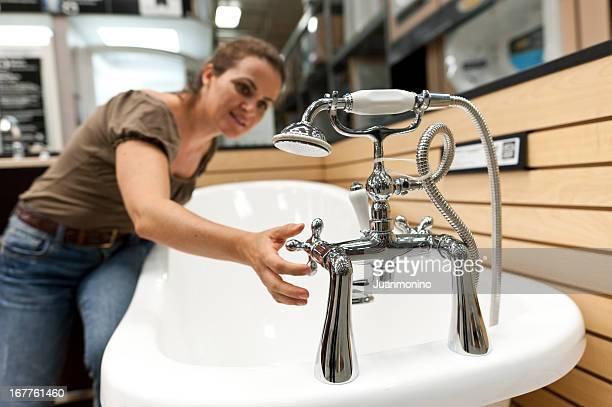 Woman Testing Bathtub Tap In Store