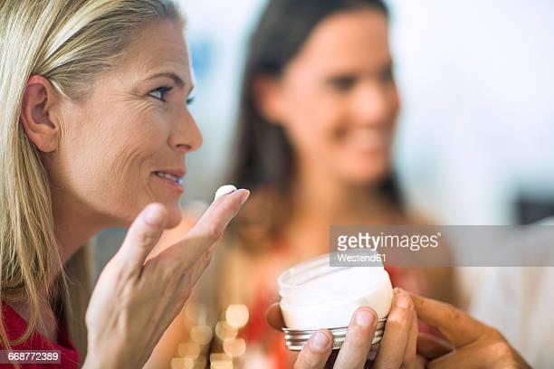 Woman testing cream in shop