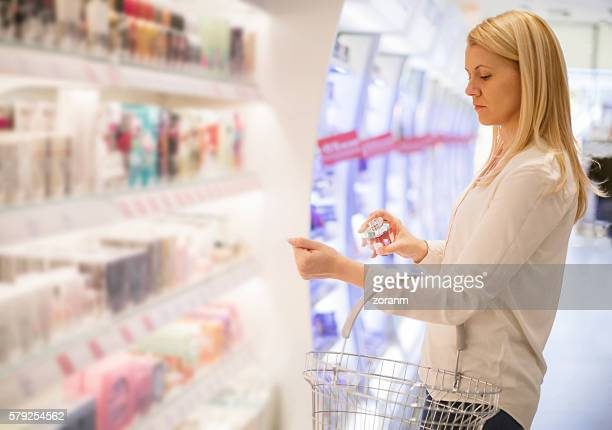 Woman testing parfume in store