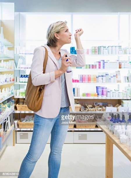 woman testing perfume in supermarket