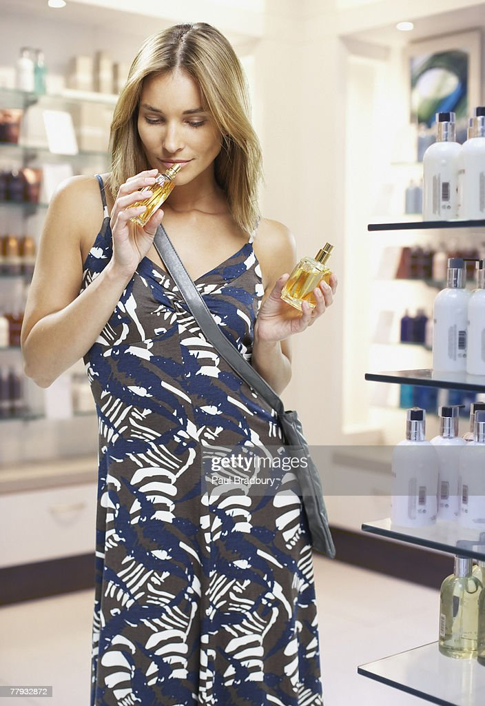Woman testing perfumes in a store : Stock Photo