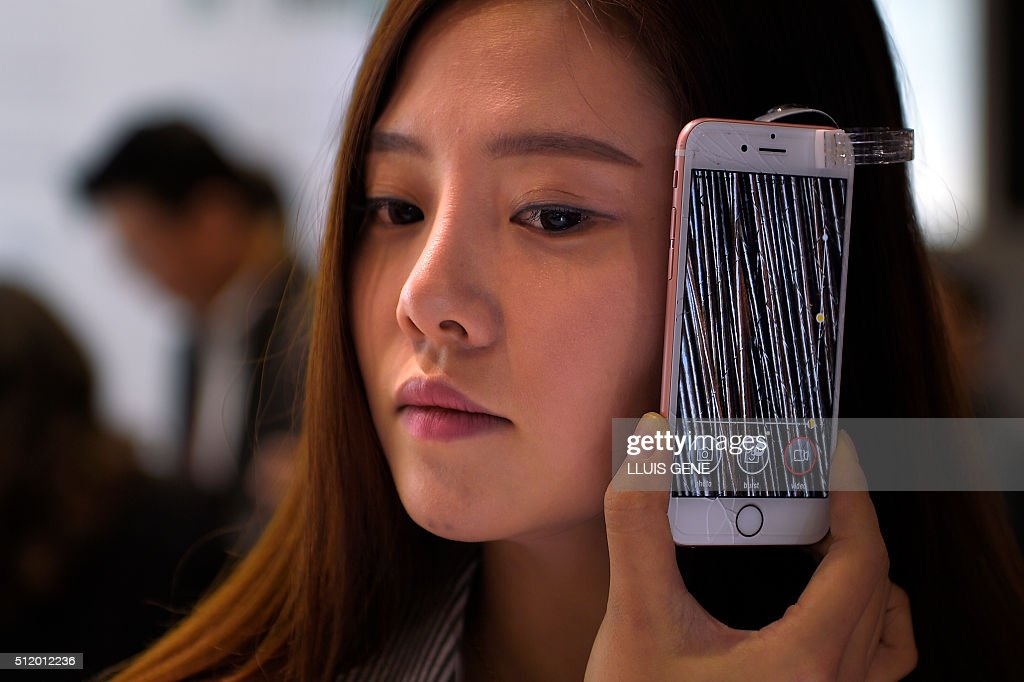 A woman tests a micro camera installed on a mobile phone showing a microscopic view of her hair on the third day of the Mobile World Congress in...