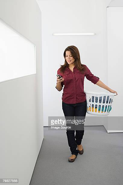 Woman text messaging and doing the laundry