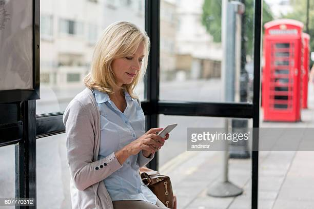 Woman texting at a bus station