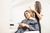 Gorgeous young woman using her smartphone and texting during her visit to a hair salon