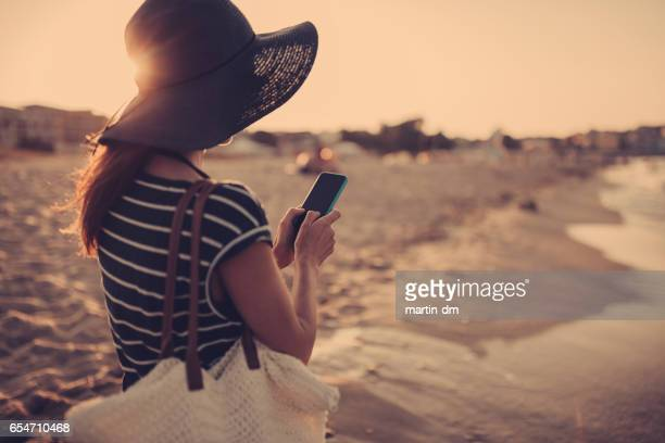 Woman texting at the beach
