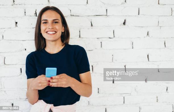 Woman texting in front of a brick wall