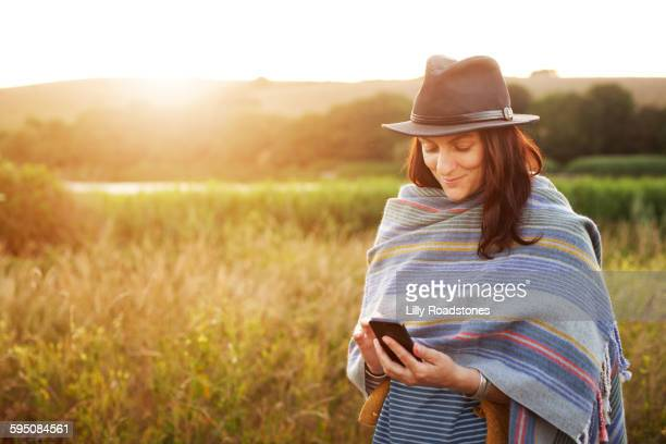 Woman texting in front of lake at sunset