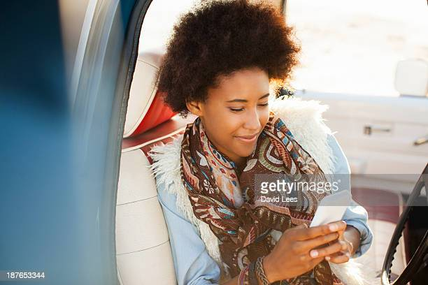 Woman texting on mobile phone in truck
