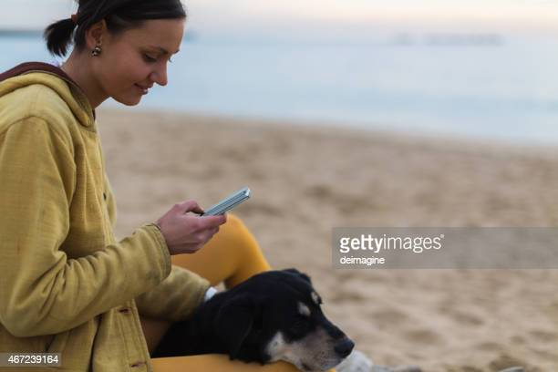 Woman texting on smart phone in the beach