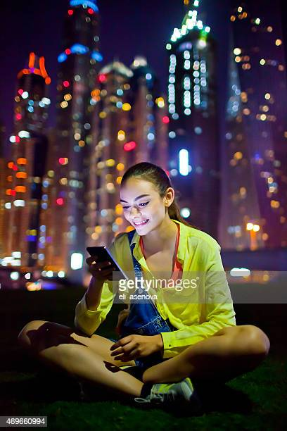Woman texting on the smart phone in Dubai Marina