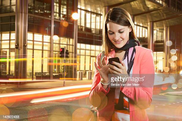 Woman texting standing in city street at night.