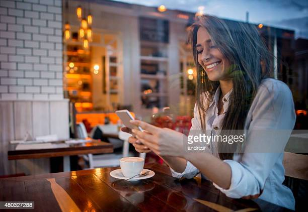 Woman texting while drinking coffee at cafe