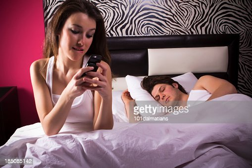 Woman texting while in bed with sleeping man