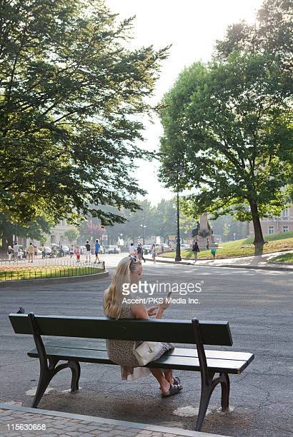 Woman texts with phone from park bench, city