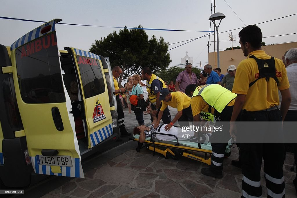 A woman that was evacuated from an area affected by wildfires lies on stretcher next to an ambulance before being taken to hospital, after 9 days of forest fires on the Spanish Canary island of La Gomera on August 13, 2012. Scores of villagers spent the night in hotels and student halls after fleeing wildfires that continued raging out of control on August 12 on the Spanish Canary Islands. AFP PHOTO / Desiree Martin