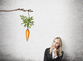 young pretty woman with her hand on chin looking up at a painted carrot tied to a branch. Concrete background. Front view. Concept of reward.