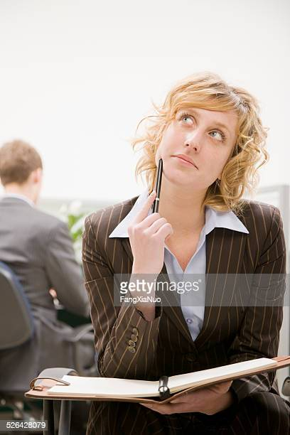 Woman Thinking at Desk With Open Notebook