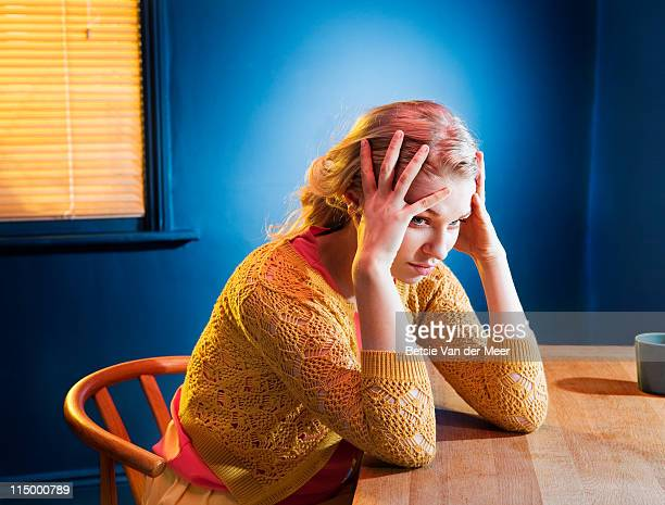Woman thinking, sitting at table.