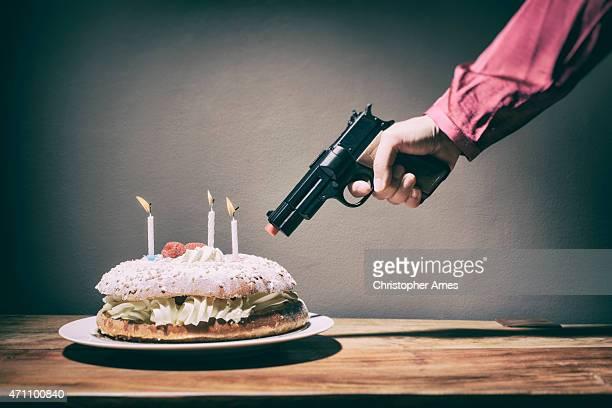 Frau droht Creme Geburtstagstorte mit Spielzeug-Hand Pistole