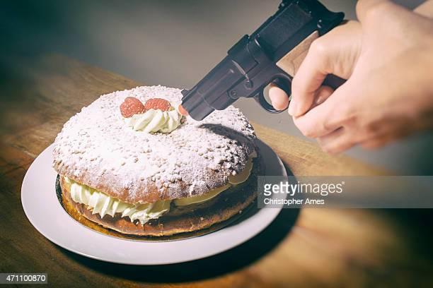 Femme met la crème délicieux gâteau à la main avec Pistolet en plastique