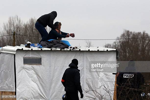 A woman threatens to cut her wrist with a knife as French police remove her and a man from the top of a hut as they clear the 'jungle' migrant camp...