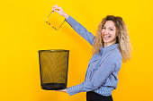 Portrait of curly-haired woman in striped shirt isolated on orange background throwing glasses she doesn't need any more into trash bin surgical correction of eyesight concept.