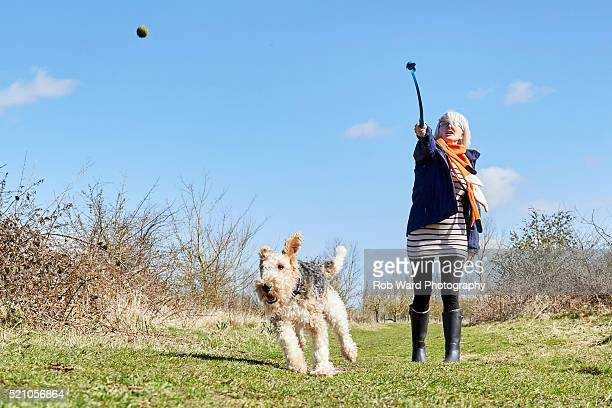 Woman throwing a ball for a dog.
