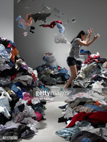 Woman throwing clothes in overflowing laundry room : Bildbanksbilder